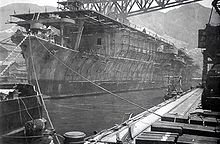 Photograph of a large ship floating in the water next to a long dock. The photograph is taken from a location on the dock in front of the ship's bow and looking back towards its stern. There are many cables and chains tying the ship to the dock. There is scaffolding all along the ship's side visible between the waterline and the ship's flat deck. A large metal structure runs horizontally from the dock to a location somewhat above the ship's upper deck. There are mountains visible in the distance behind the ship and the dock, and some sky is visible above the mountains.