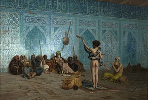 This painting shows the back side of a naked man standing with a snake wrapped around his waist and shoulders. The man is lifting up the head of the snake with his left hand. Another man to his right is sitting on the ground playing a pipe. A group of 10 men are sitting on the floor facing the snake handler with their backs against an ornate blue mosaic wall decorated with Arabic calligraphy.