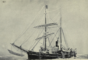 Two-masted sail-and-steam ship, with pennant flying from topmast, sails furled, lying stationary in a frozen sea