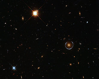 General relativity - This blue horseshoe is a distant galaxy that has been magnified and warped into a nearly complete ring by the strong gravitational pull of the massive foreground luminous red galaxy.