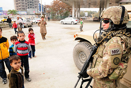 An American soldier standing with children at Freedom Circle (2011) Local soldier mentors Afghan police in Kabul.jpg