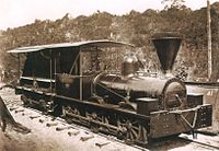 An old photograph showing a shiny black engine having a cab with open sides and a large, funnel-shaped smokestack