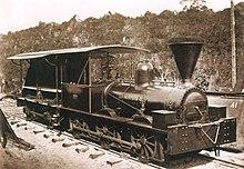 Uma fotografia velha que mostra uma locomotiva preto brilhante com um táxi com lados abertos e um grande chaminé em forma de funil