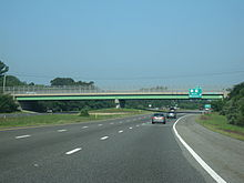 Ground-level view of a three lanes of a divided freeway; a large green and gray overpass bridge and a green exit sign are visible in the distance.