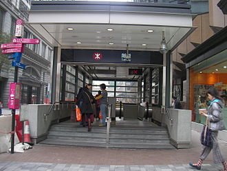Middle Road, Hong Kong - Exit L3 of Tsim Sha Tsui Station in the west section of Middle Road, at the corner of Nathan Road. The back of the Peninsula Hotel is visible on the left; the Kowloon Hotel is on the right.