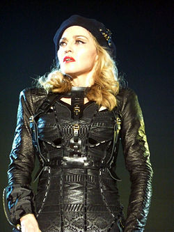 A middle-aged blond woman wearing a black leather full-sleeved dress, and a cap on her head