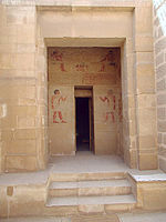 Rear wall of a vestibule in the tomb is visible through a doorway. On this wall, above and to the sides of a second door leading farther into the tomb, are murals painted in color. They show Khnumhotep and Niankhkhum seated at table above the second door, then they stand facing one another across the second door, each holding his staff of authority.