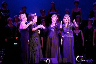"""Sweet Adelines International competition - Reigning quartet champions MAXX Factor performing in 2011, wearing their 2010 championship crowns. Note, past """"queens"""" in the background with their own, different, crown styles"""