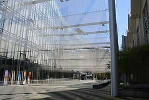 Seattle Opera - The facade of Marion Oliver McCaw Hall at Seattle Center, seen from Kreielsheimer Promenade, with the Space Needle in the background