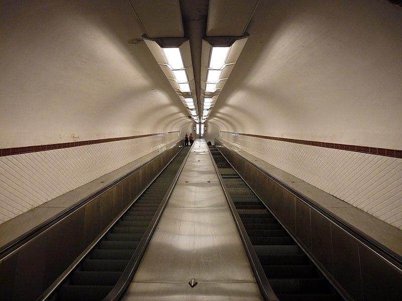 Photo 4/3 symétrique d'un l'escalier mécanique, vide, avec un point de fuite central.