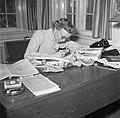 Mevrouw Svendsen schrijvend aan een bureau waarop boeken en botten liggen, Bestanddeelnr 252-8750.jpg