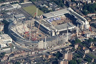 Tottenham Hotspur Stadium - Northern section of the new stadium (left) under construction in May 2017, West Stand of White Hart Lane (right) partially demolished. The new ground covers part of the old ground.
