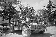 Large group of soldiers sitting on an armoured car