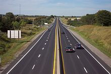 """A photo of a four-lane divided highway on a sunny day. The photo is taken from a position above the centre of the highway, which continues forward into the horizon. Several cars can be seen on the highway. An offramp on either side of the highway merges with it halfway up the picture."""