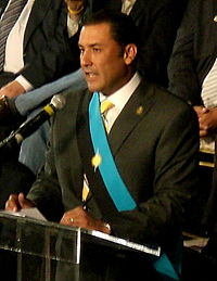 A black suited man talking to an audience in front of a microphone