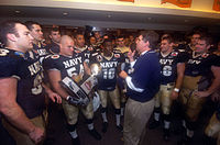 A middle aged man in a blue polo shirt and khaki pants speaks to young men in football uniforms in the locker room. One of the men is holding a trophy.