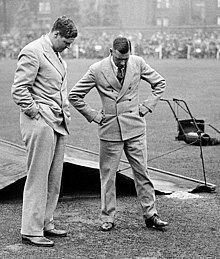 Two men inspect the ground on a wet cricket pitch
