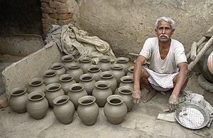 Potter and his work, Jaura, India.jpg