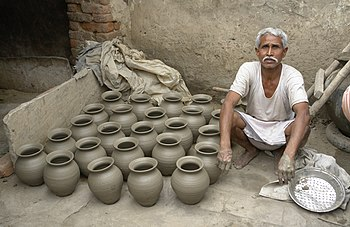 Potter and his work, Jaura, India.jpg