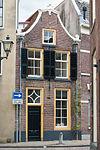foto van Pand met klokgevel met verdiepingramen met stores en met rollagen boven ramen en deur