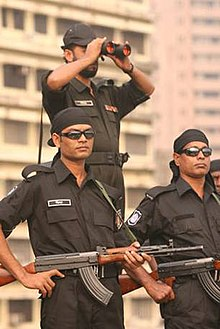 Armed men in black uniforms on a street