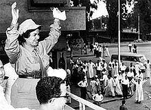 A woman in her thirties dressed in military garb waves to a crowd of supporters.