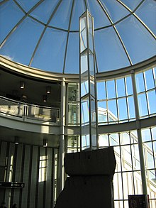 A tall prism sculpture in a glass atrium.