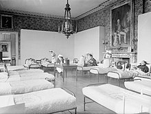 A room converted into a hospital ward with nurses and patients in beds