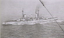 A light gray battleship steams in choppy seas.