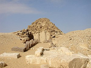 Heavily eroded pyramid with stone blocks and ruins in front