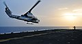 Sailor directs an AH-1 Cobra helicopter to take off from USS Boxer (5805296400).jpg