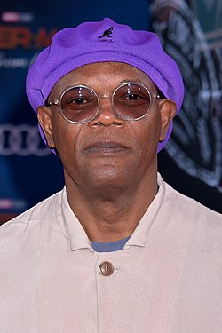 An African-American man is at the centre of the image looking at the camera. He is wearing a purple cap, glasses, and an off-white coat.