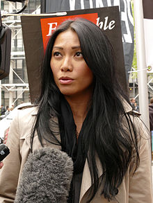 A black-haired woman with a grey coat getting interviewed