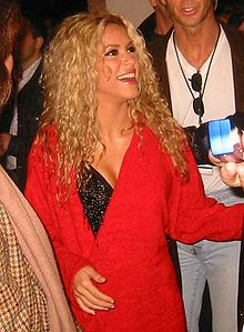 A woman with curly golden hair is dressed in a red jacket over a black top. She is looking upwards and laughing.