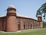 Building of red bricks with a roof consisting of many white domes. There are small round towers on the corners of the building each crowned by a white cupola.