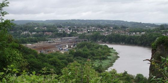 View towards the site of the former National Shipyard No.1, in the area covered by the factory buildings and overgrown slipways in the centre of the photograph Shipyard site chepstow cropped.jpg