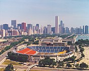 An aerial view of Soldier Field with the Chicago skyline in the background
