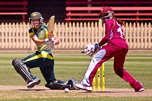 Women's cricket - An Australian batter hits a shot, while a West Indies wicket-keeper looks on, during a women's cricket match, 2014