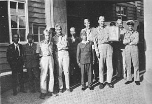 A group of men in uniforms stand in front of a wooden building. One, holding a box, is very tall, towering over the Asian man next to him.