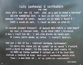 Ballylaneen - Inscription on the gravestone for Tadhg Gaelach Ó Súilleabháin originally composed by Donnacha Rua in latin (carved on the gravestone) and translated to Irish shown on the black plaque (above) by teacher Tom Walsh around 1910.