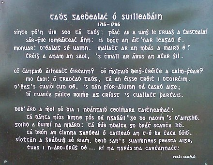 Inscription on the gravestone for Tadhg Gaelach Ó Súilleabháin originally composed by Donnacha Rua in latin (carved on the gravestone) and translated to Irish shown on the black plaque (above) by teacher Tom Walsh around 1910.