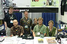 Five men and a woman in a convention booth for Telltale Games. A variety of Sam & Max merchandise is on the table in front of them.