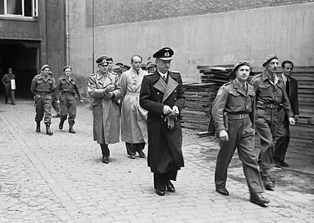 Leading members of the Flensburg Government after their arrest. Karl Dönitz (centre, in long, dark coat) is followed by Speer (bareheaded) and Alfred Jodl (to the left of Speer). - Albert Speer