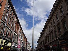 Tall pole rising high into the sky above buildings lining a city centre shopping street