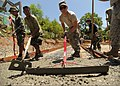U.S. Air Force Airman 1st Class Matthew Farnworth, center, uses a cementing rake to spread concrete for the foundation of a new schoolhouse April 1, 2013, in Omaya, Philippines 130401-N-VN372-115.jpg