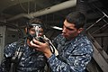 U.S. Navy Ship's Serviceman Seaman Recruit Jesse Turtenwald, right, an in-port emergency team member, assists Logistics Specialist Seaman Recruit Eduardo Mendivil with donning his self-contained breathing 131030-N-XP477-022.jpg