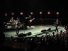 A colorful, round stage inside an arena, with all four of the band members performing their instruments.
