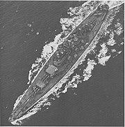 A large battleship steams through choppy seas. Three floatplanes are located on the stern.