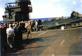 USS Sangamon (CVE-26) - On 4 May 1945, at 1933, Sangamon was hit by a kamikaze aircraft. This photo the next day shows both aircraft elevators have been blown out of place by explosions below. At this time the only functional radio aboard was in the last surviving aircraft, an F6F Hellcat missing most of its starboard wing.