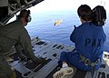 US Navy 021220-N-7590D-025 U.S. Coast Guard air crewman looks on as Bill Paris, a commercial cameraman captures footage of an HH-65A Helicopter.jpg